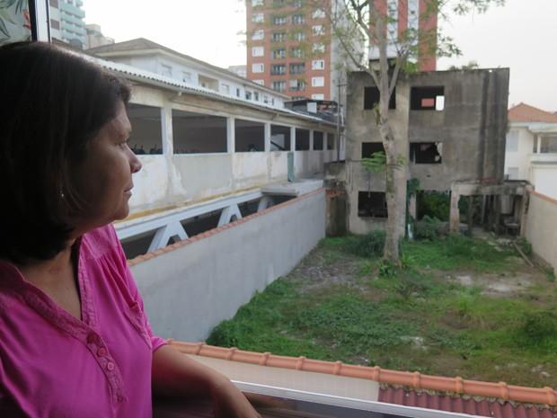 Edna olha o local onde o avião caiu, em Santos (Foto: Mariane Rossi/G1)