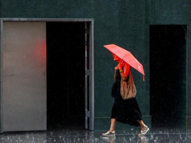Mulher caminha sob chuva em Manhattan, em Nova York; estudo confirmou relação entre clima chuvoso e aumneto de dores  (Foto: Reuters/Eduardo Munoz)