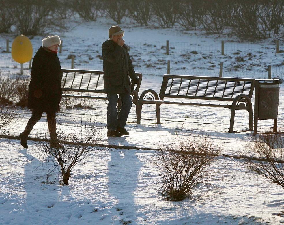 Pessoas caminham no parque Kepa Potocka, em Varsóvia, na Polônia, coberto de neve, nesta segunda-feira (9)  (Foto: Czarek Sokolowski/ AP)