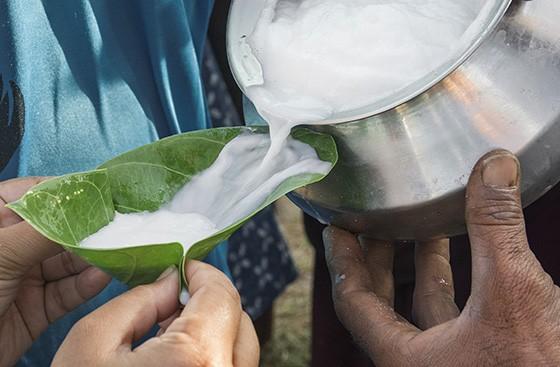 O leite armazenado no pote chamado chada é depois distribuído em copinhos feitos com a folha da planta aak  (Foto: © Haroldo Castro/ÉPOCA)