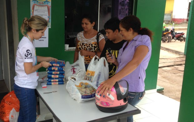 A Analista de Marketing da TV Amapá fazendo a troca dos alimentos por ingresso (Foto: Celso Kato/TV Amapá)