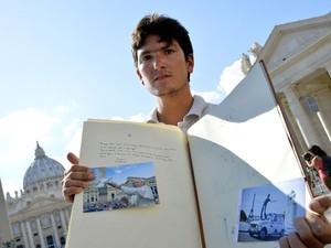 Vincent com o livro de couro preenchido com mensagens de cristãos e do Papa Francisco (Foto: Andreas Solaro/AFP)
