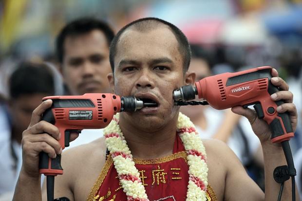 Participante fura bochechas com furadeiras em festival na Tailândia