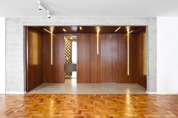 As paredes e o teto deste hall de entrada, decorado pela Tria Arquitetura, foram revestidos com ripas de cumaru, formando uma grande caixa de madeira (Foto: Maíra Acayaba / Divulgação)