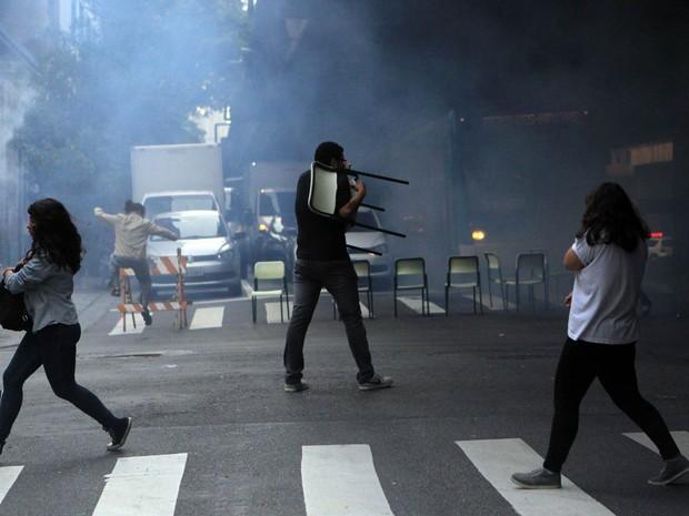Estudantes da Escola Estadual Fidelino Figueiredo fogem com cadeiras após policiais atirarem bomba de gás lacrimogêneo. Os alunos haviam bloqueado o cruzamento da Avenida São João com a Avenida Angélica, em Santa Cecília, Zona Oeste de São Paulo (Foto: Werther Santana/Estadão Conteúdo)
