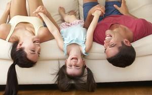 Como aproveitar bem o tempo com os filhos casal se diverte com a filha no sofá Minha Vida Anda