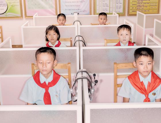 Crianças em aula de inglês numa escola para órfãos. A ordem e os uniformes impecáveis formam um cenário, no qual elas agem como atores do regime (Foto: Max Pinckers)