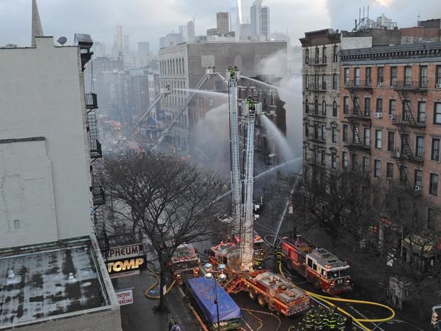 Bombeiros trabalham para combater incêndio em prédio no East Village, no distrito de Manhattan, em Nova York (Foto: Louis Lanzano/AP)