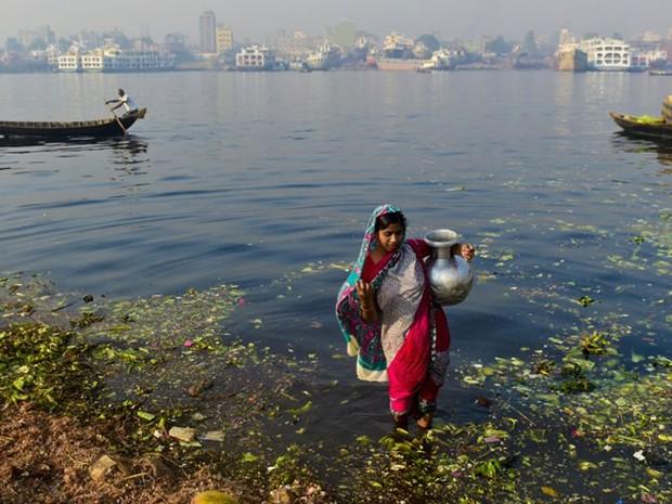 Mulher coleta água contaminada no rio Buriganga, em Dhaka, em Bangladesh. Foto data de 19 de março de 2015 (Foto: Munir Uz Zaman / AFP)