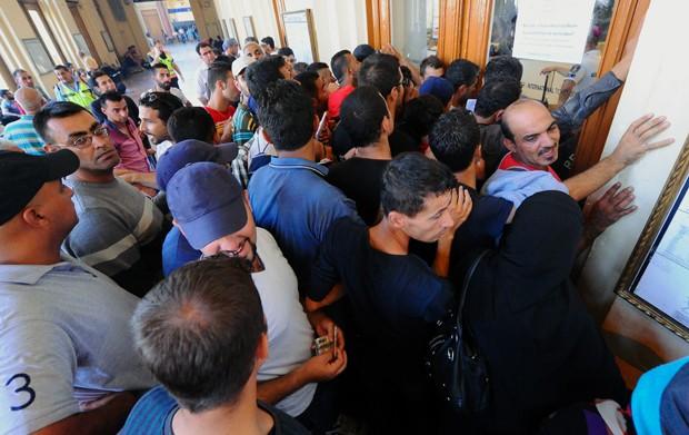 Migrantes aguardam em frente a posto de venda de bilhetes em estação de trem de Budapeste, na Hungria (Foto: Attila Kisbenedek / AFP)
