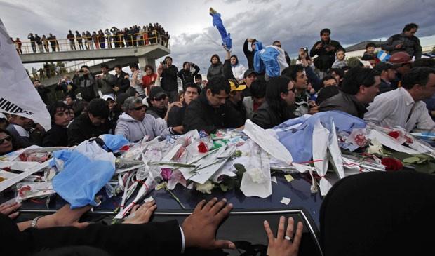 População de Rio Gallegos, cidade natal do ex-presidente Néstor Kirchner, cerca o carro funerário com o caixão, nesta sexta (29) (Foto: Natacha Pisarenko / AP)