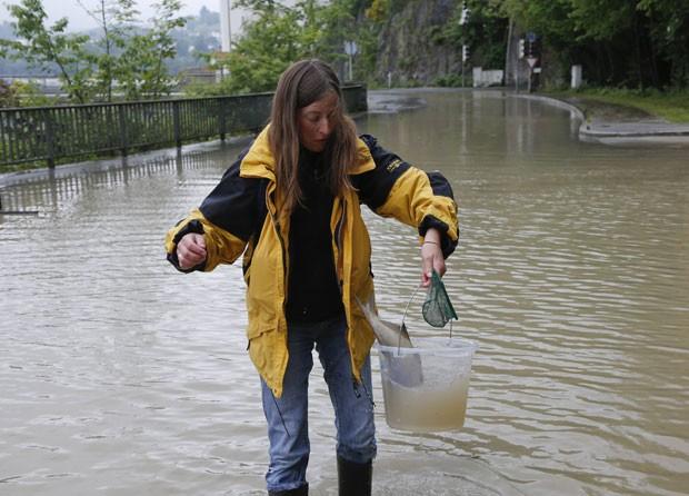 Após pegar o peixe, a mulher o devolveu ao rio que desbordou por causa das fortes chuvas (Foto: Wolfgang Rattay/Reuters)