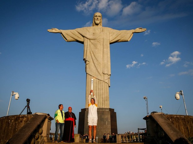 A ex-jogadora de vôlei Isabel ergue a tocha olímpica diante do Cristo Redentor, no Rio de Janeiro, acompanhada pelo prefeito Eduardo Paes e pelo arcebispo do Rio, o cardeal Dom Orani Tempesta (Foto: Thiago Bernardes/Framephoto/Estadão Conteúdo)