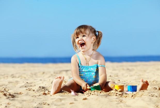 Criança brincando na areia da praia (Foto: Shutterstock)