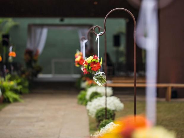 Suportes de ferro, de onde pendiam vasinhos de vidro com flores, cercavam os dois lados da passarela. No chão, cestas intercalavam o branco dos mosquitinhos com o verde das folhagens. A decoração ficou a cargo de Márcio da Silva, da Casa Aragon (Foto: Coletivo 3)