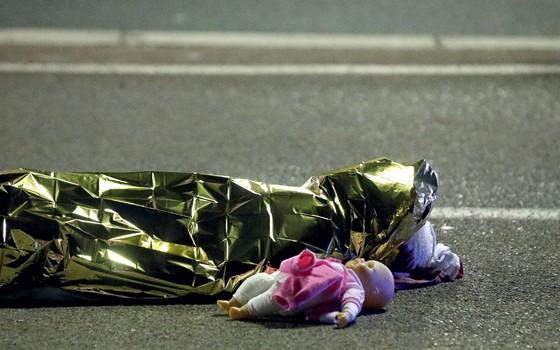 boneca ao lado de uma das vítimas  (Foto:  Eric Gaillard / Reuters)