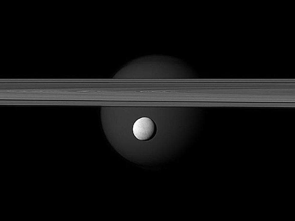 Fotografia mostra a lua Encélado à frente da lua Titã. Entre elas aparecem os famosos aneis de Saturno. A fotografia foi feita pela sonda espacial Cassini em 12 de março e divulgada nesta quinta-feira (10) pela Nasa. (Foto: NASA/JPL-Caltech/Space Science Institute)
