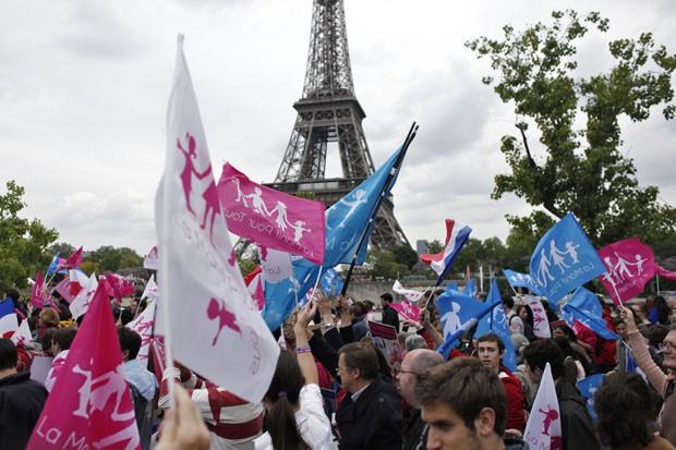Manifestantes exibem bandeiras em protesto após a celebração da primeira união civil de um casal gay (Foto: Laurent Cipriani/AP)