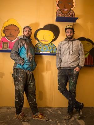 Otávio e Gustavo Pandolfo, Osgêmeos, em frente a uma obra da exposição 'A ópera da Lua' (Foto: Guilherme Tosetto/G1)