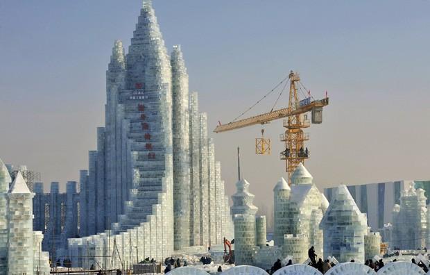 Estrutura que relembra prédio é visto em meio a trabalhadores e guindaste durante montagem do 30º Festival de Gelo e Neve de Harbin (Foto: Sheng Li/Reuters)