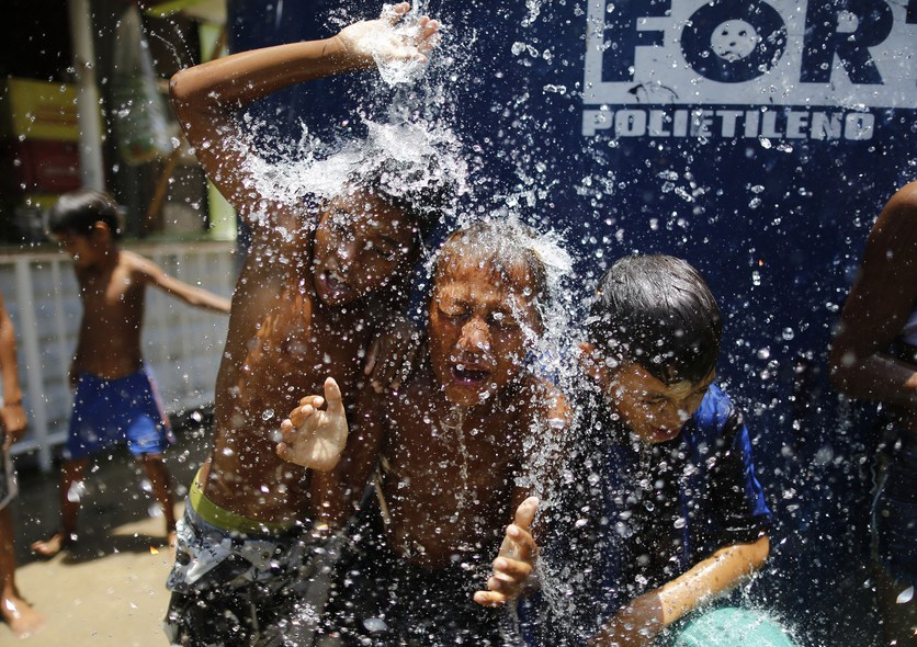 Children play under the water that they manage to spill over from a water tank, to cool off from the summer heat, at the Alemao Complex slum in Rio de Janeiro, Brazil, Thursday, Jan. 29, 2015. State Environment Secretary Andre Correa acknowledged the regi