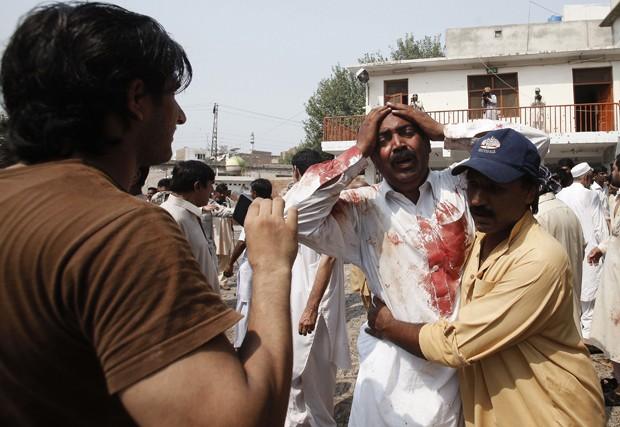 Homem chora após a morte de seu irmão no local de um atentado suicida em uma igreja em Peshawar, no Paquistão (Foto: Fayaz Aziz/ Reuters)