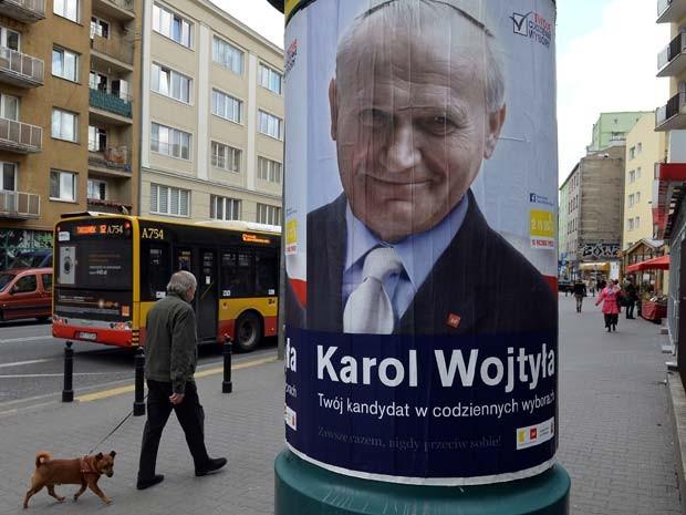 Centro de Varsóvia, na Polônia, tem postes com cartazes de João Paulo II de soléu, terno e gravata (Foto:  AFP PHOTO / JANEK SKARZYNSKI)
