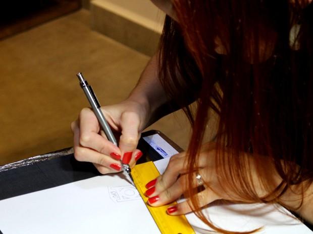 Tatuadora prepara tatuagem de 'mureta e 013' em Santos (Foto: Orion Pires / G1)