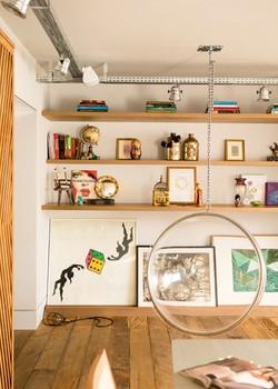 Living | À frente, fica a Bubble Chair (1968), de Eero Arnio, na Micasa. No chão, sob as prateleiras com livros e objetos, destacam-se a obra de Allex Valauri, no canto à esq., e uma de Alfredo Volpi, no canto à dir. (Foto: Edu Castello/Editora Globo)