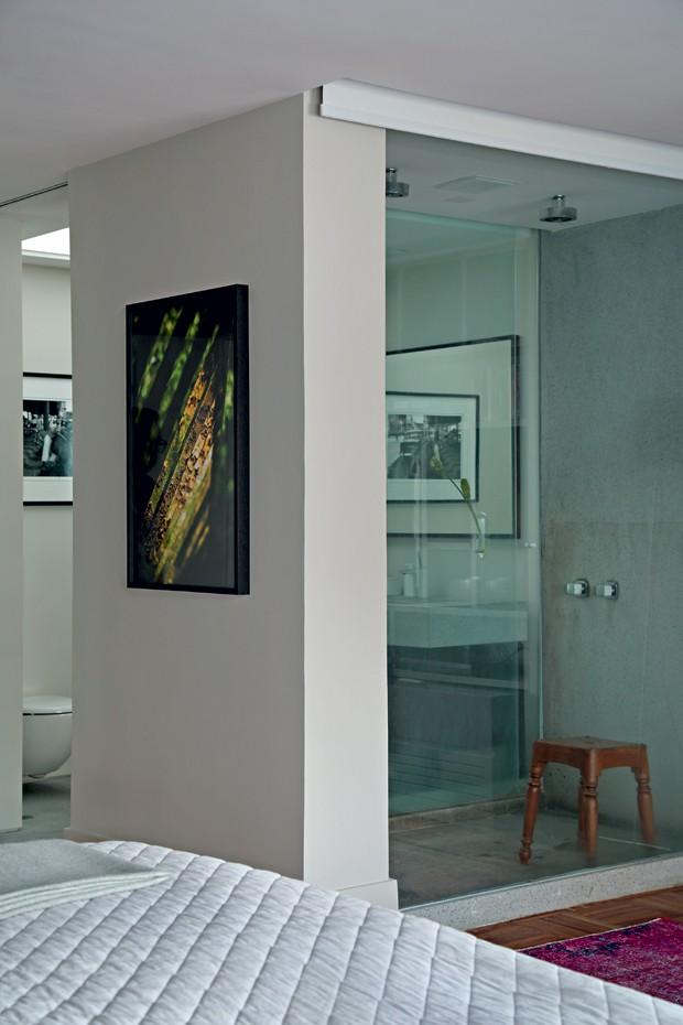 Banheiro. Um pano de vidro deixa a área do boxe aparente. Louças e metais da Hansgrohe, na Vallvé. Na parede, foto clicada pelo proprietário (Foto: Denilson Machado / MCA Estúdio / Divulgação)
