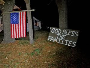 """Na rua da escola Sandy Hook. Vizinhos fincaram bandeiras dos EUA nos jardins e escreveram """"Deus abençoe as famílias"""" (Foto: AP)"""