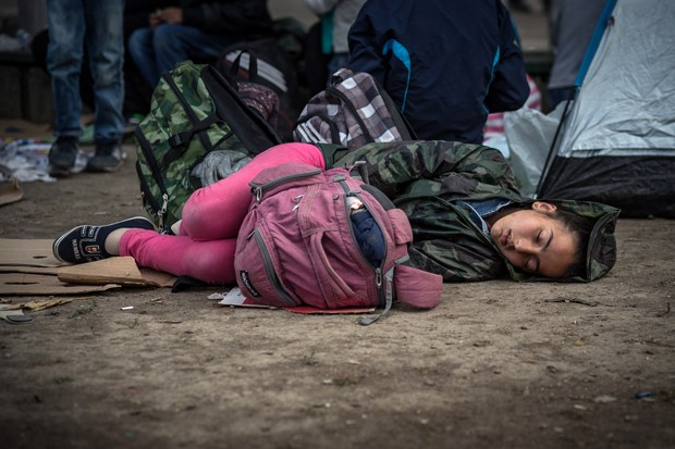 Jovem dorme no chão em área onde migrantes encontraram abrigo temporário em Belgrado (Foto: Andrej Isakovic / AFP)