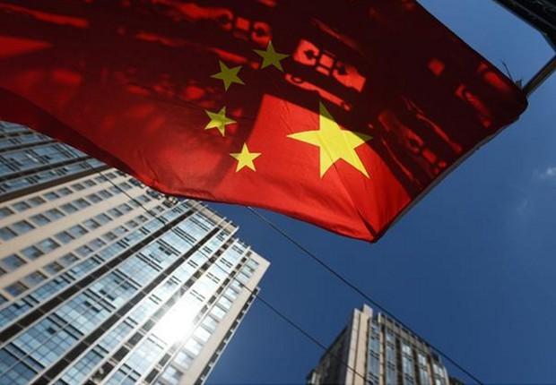 Bandeira chinesa tremula perto de um conjunto de apartamentos em Pequim ; PIB da China ; produção industrial da China ; economia da China ;  (Foto: Greg Baker/AFP/Getty Images)