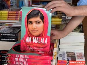 Funcionário de uma livraria de Islamabad exibe cópias da autobiografia da ativista paquistanesa Malala Yousafzai (Foto: Aamir Qureshi/ AFP)