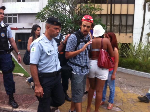 Policial acompanha homem expulso da Marcha das Vadias em Brasília (Foto: Rafaela Céo/G1)