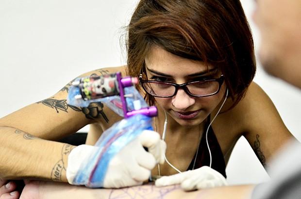 Malu Duarte tatuando Rafael Godinho (Foto: Roberto Teixeira/EGO)