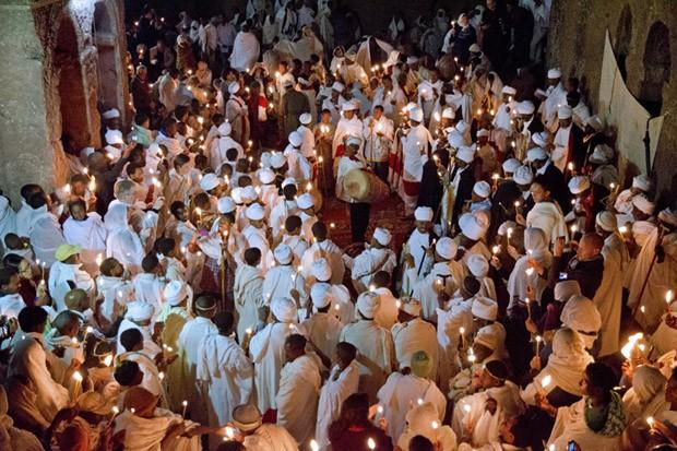 Um pouco antes da meia-noite, um sacerdote traz uma vela do interior de Bet Maryam e distribui a chama para seus irmãos de confraria (Foto: © Haroldo Castro/Época)