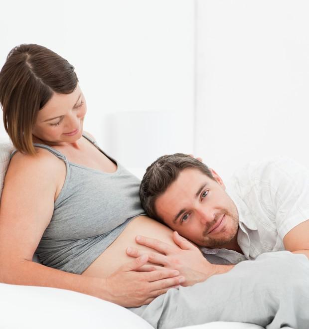 Pai sente a barriga da grávida (Foto: Thinkstock)