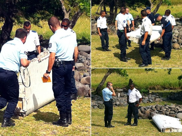 Um pedaço de destroços que parece ser parte da asa de um avião é levado por policiais após ser achado na ilha francesa de Reunião, levando a especulações de que seria do voo MH370 da Malaysia Airlines, desaparecido em março de 2014 (Foto: Yannick Pitou/AFP)