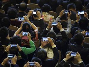 Público usa smartphones durante o encontro da Apec de 2014. (Foto: Andy Wong/Associated Press)