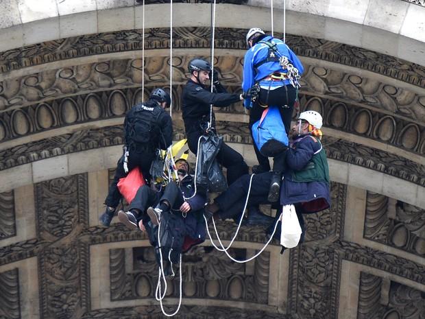 Policiais franceses prendem ativistas do Greenpeace que faziam um protesto no Arco do Triunfo em Paris (Foto: Franck Fife/AFP)