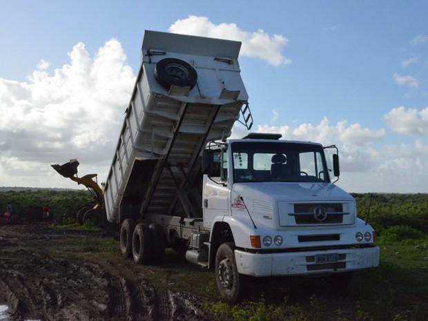 Caminhão conta com ajuda de trator para despejar o resultado da limpeza de galerias da cidade. (Foto: Aline Oliveira/G1)