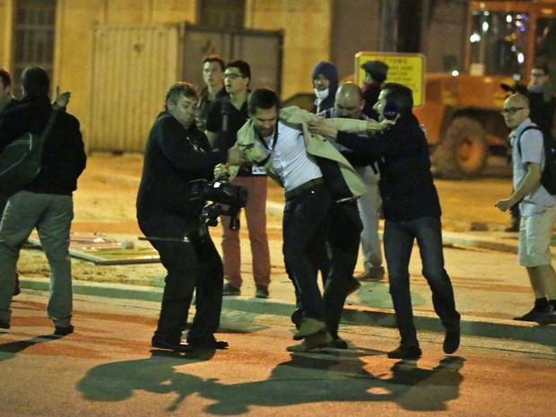 Um cinegrafista é agredido por membros do movimento anti-casamento gay durante uma manifestação em Paris. (Foto: Kenzo Tribouillard/AFP)