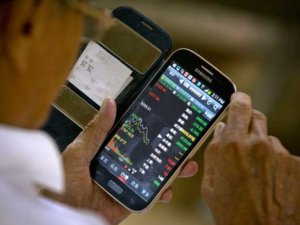 Investidor usa smartphone para monitorar ações na China (Foto: Mark Schiefelbein / AP Photo)