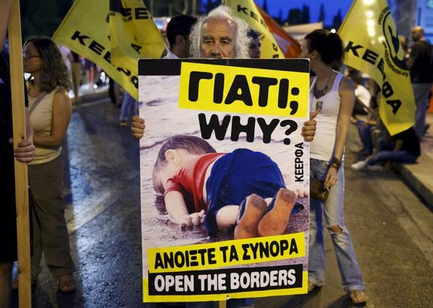 GRÉCIA: Um homem segura um carta com a foto do menino Aylan Kurdi, que morreu na tentativa de chegar de barco, com a família, até a Grécia, durante protesto a favor da recepção de imigrantes em Atenas (Foto: Reuters/Paul Hanna)