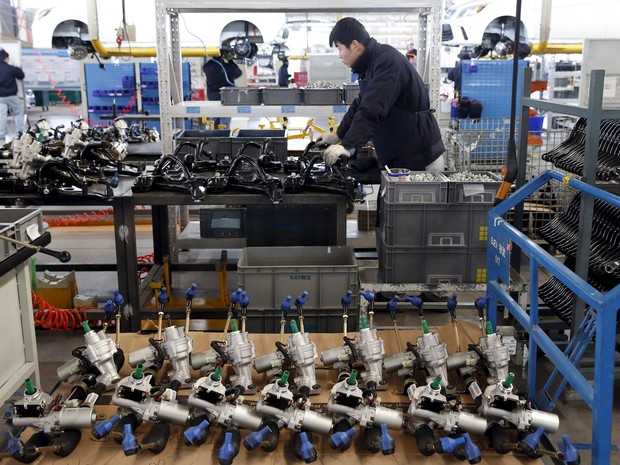 Empregado trabalha em linha de montagem de carros eletrônicos em Pequim (Foto: Kim Kyung-Hoon/Reuters)