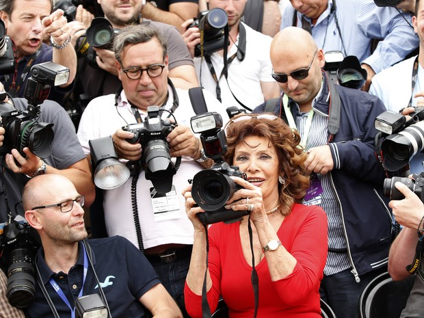 Sophia Loren segura uma câmera ao lado dos fotógrafos na edição 67 do Festival de Cannes (Foto: AP/Alastair Grant)