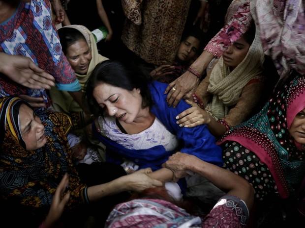 Mulheres tentam consolar uma mãe que perdeu o filho no atentado a bomba que tinha cristãos como alvo durante o final de semana em Lahore, no Paquistão. O ataque suicida deixou dezenas de mortos e centenas de feridos durante festa da Páscoa (Foto: K.M. Chaudary/AP)