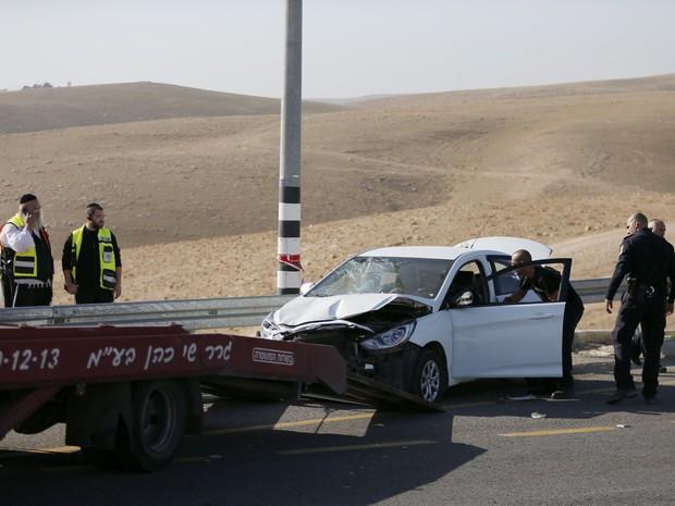 Polícia israelense retira carro usado por palestino para tentar atropelar policiais. Motorista foi morto em ação nesta sexta-feira (27) na Cisjordânia (Foto: Ammar Awad/Reuters)