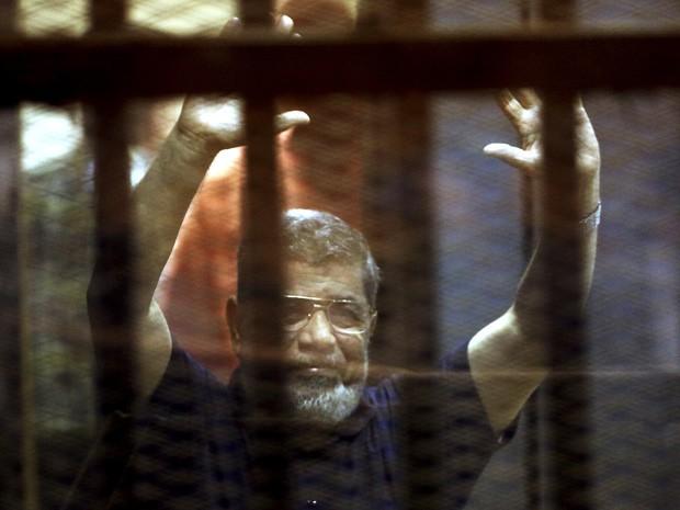 Ex-presidente do Egito Mohamed Morsi acena atrás das grades em um tribunal na periferia do Cairo, neste sábado (16) (Foto: REUTERS/Mohamed Abd El Ghany)